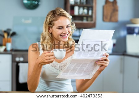 Smiling beautiful woman reading newspaper at home - stock photo