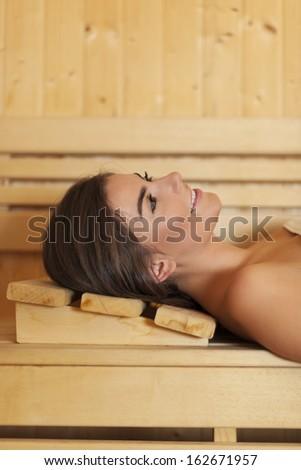 Smiling beautiful woman resting in sauna  - stock photo