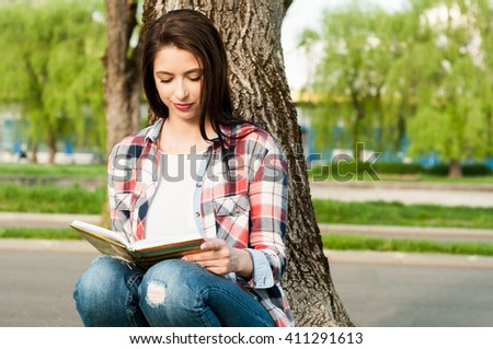 Smiling beautiful woman sitting under tree on sunny day, relaxing and reading a book in the park - stock photo