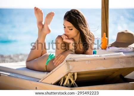 Smiling beautiful woman sunbathing in a bikini on a beach at tropical travel resort,enjoying summer holidays.Young woman lying on sun lounger near the sea.Happy serene woman having SPF protection - stock photo