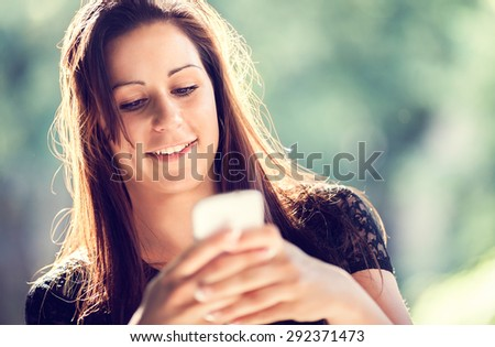 Smiling beautiful woman texting with her mobile phone. Toned photo, shallow depth of field. - stock photo