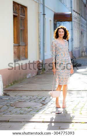 smiling beautiful woman with a small handbag on the ancient street - stock photo