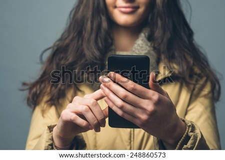 Smiling beautiful woman with smart phone text messaging - stock photo