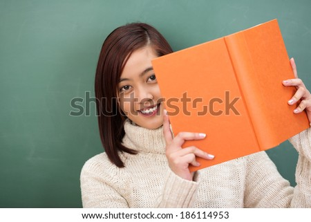 Smiling beautiful young Asian student peering around the side of her orange textbook as she stands in front of the class chalkboard - stock photo