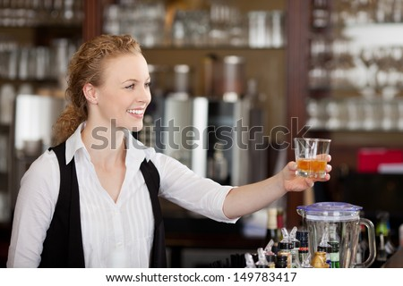 Smiling beautiful young barmaid serving alcohol in a tumbler to a client across the top of the bar counter - stock photo