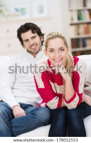 Smiling beautiful young blond woman relaxing at home with her husband sitting leaning forwards on a sofa looking at the camera with a friendly smile - stock photo