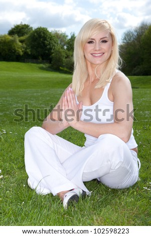 Smiling beautiful young blonde woman sitting cross-legged on green grass with her hands clasped in a yoga pose - stock photo