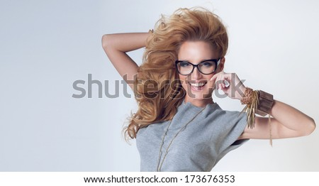 Smiling beautiful young blonde woman with curly hair posing wearing jewelry and glasses. - stock photo