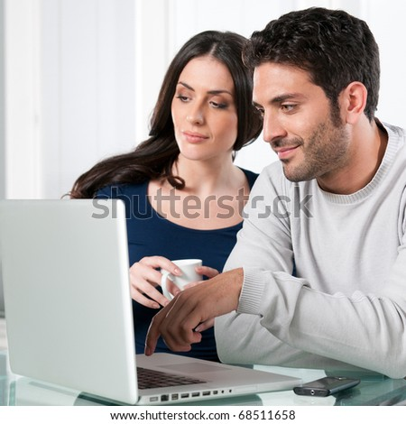 Smiling beautiful young couple surfing the net with laptop at home - stock photo