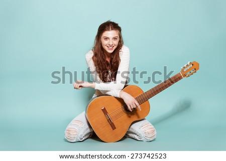 smiling beautiful young girl posing with guitar - stock photo