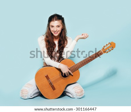 smiling beautiful young girl posing with guitar - stock photo