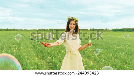 Smiling beautiful young woman blowing soap bubbles on summer meadow - stock photo
