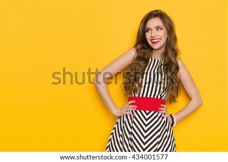 Smiling beautiful young woman in black and white striped dress posing with hands on hip and looking away. Three quarter length studio shot on yellow background. - stock photo
