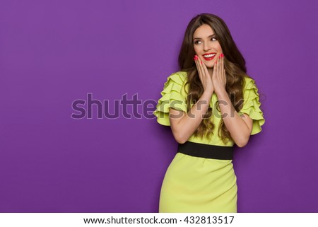 Smiling beautiful young woman in lime green dress posing with hands on chin and looking away. Three quarter length studio shot on purple background. - stock photo