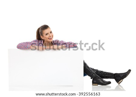 Smiling beautiful young woman in lumberjack shirt and black boots, sitting on floor behind white placard and looking at camera. Full length studio shot isolated on white. - stock photo
