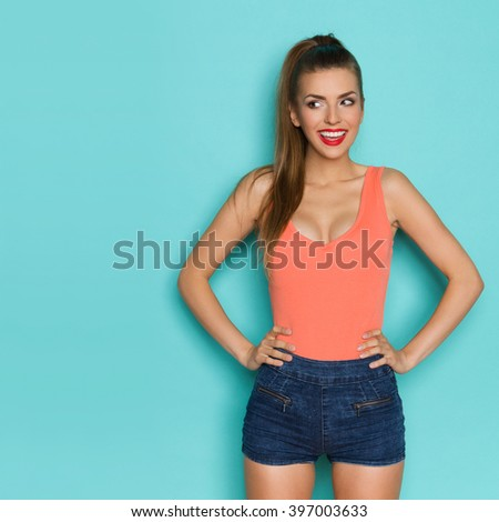Smiling beautiful young woman in orange shirt and jeans shorts posing with hands on hip and looking away at copy space. Three quarter length studio shot on teal background. - stock photo