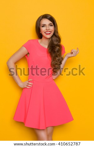 Smiling beautiful young woman in pink mini dress posing with hand on hip. Three quarter length studio shot on yellow background. - stock photo