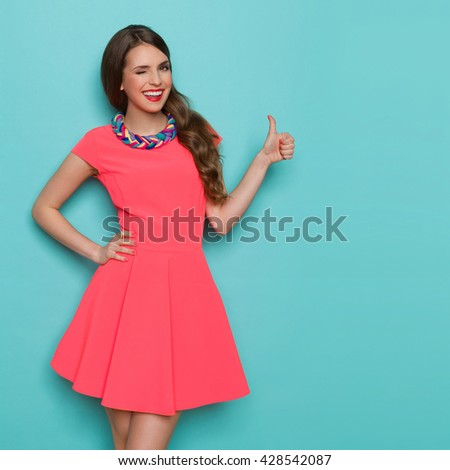 Smiling beautiful young woman in pink mini dress showing thumb up and winking. Three quarter length studio shot on turquoise background. - stock photo