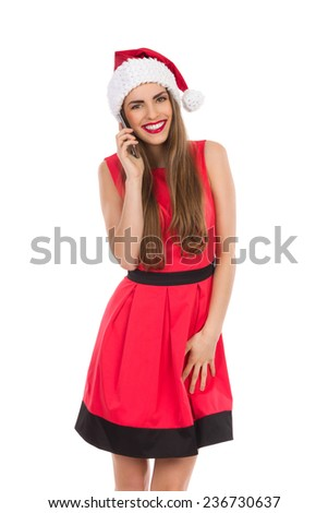 Smiling beautiful young woman in red santa's hat and dress using cell phone. Three quarter length studio shot isolated on white. - stock photo