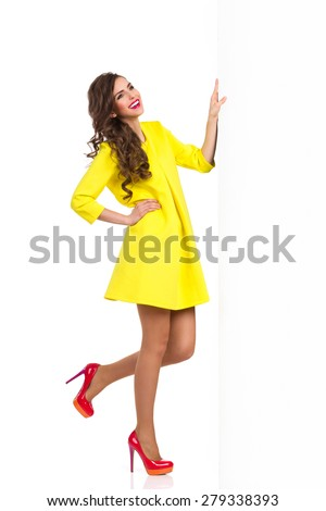 Smiling beautiful young woman in yellow dress and red high heels standing on one leg and holding a big banner. Full length studio shot isolated on white. - stock photo