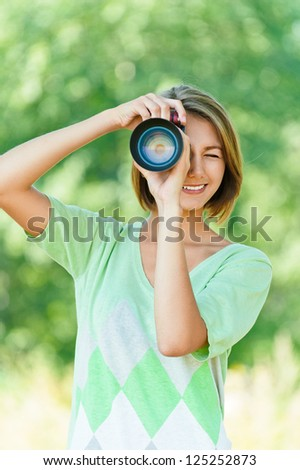Smiling beautiful young woman photographed SLR camera, against background of summer green park. - stock photo