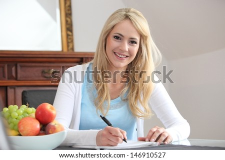 Smiling beautiful young woman sitting writing in her dining room at the table with a large colourful bowl of fresh fruit alongside for a healthy snack - stock photo