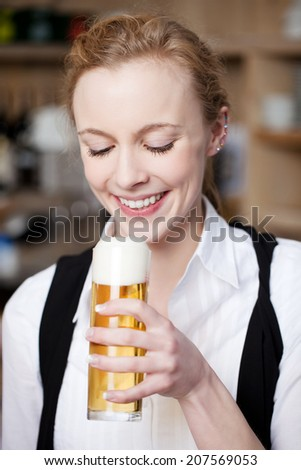 Smiling beautiful young woman with a pint of frothy beer in a her hand looking at it with anticipation - stock photo