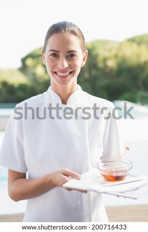 Smiling beauty therapist looking at camera holding plate with honey outside at the spa - stock photo