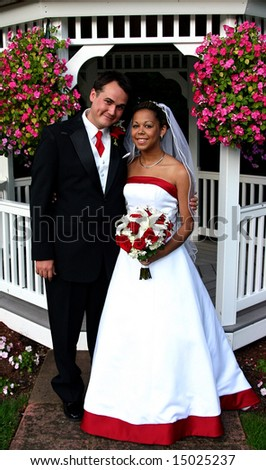 Smiling bi-racial bridal couple with red highlights - stock photo