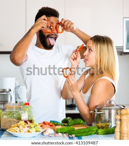 Smiling black husband helping young white wife preparing healthy dinner - stock photo