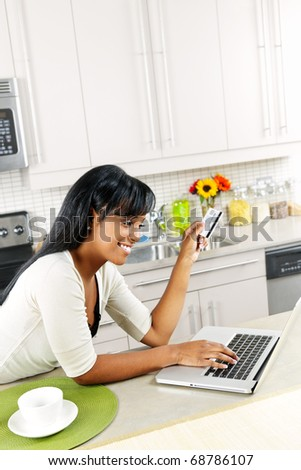 Smiling black woman online shopping using computer and credit card in kitchen - stock photo