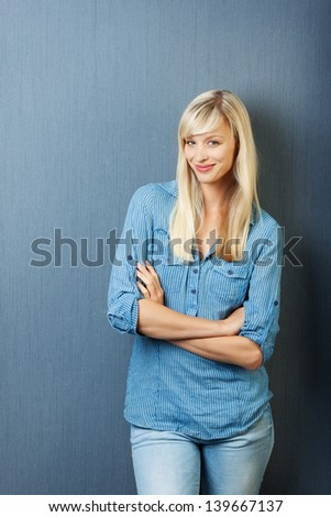Smiling blond female posing with arm crossed isolated on - stock photo
