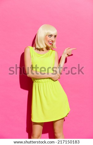 Smiling blond girl in lime dress showing pointing. Three quarter length studio shot on pink background. - stock photo