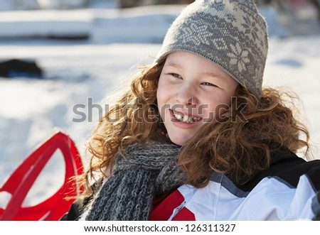 Smiling blond girl in winter cloths sitting on a bench in winter snowy park - stock photo