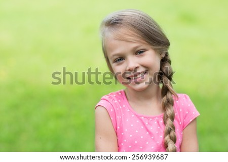 Smiling blond girl with braid. Girl seven years. - stock photo