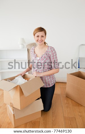 Smiling blond-haired woman preparing to move house - stock photo