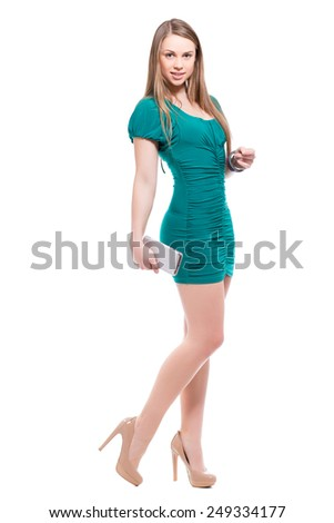 Smiling blond woman with smartphone posing in blue dress. Isolated on white - stock photo