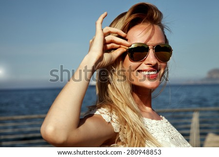 Smiling blonde attractive woman posing in sunglasses. Ship on the sea on background. - stock photo