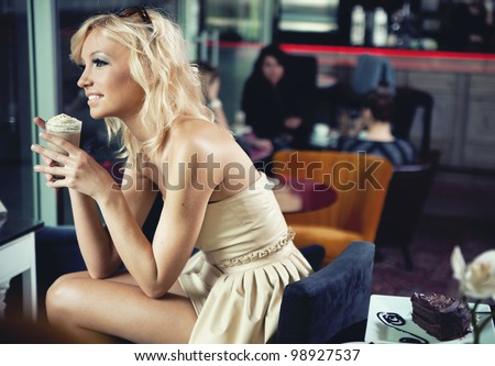 Smiling blonde beauty in a coffee shop - stock photo