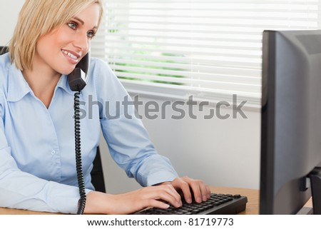 Smiling blonde businesswoman on the phone while typing looks at screen in her office - stock photo