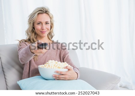 Smiling blonde changing tv channel while eating popcorn at home in the living room - stock photo