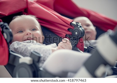 Smiling blonde couple baby seated on stroller - stock photo