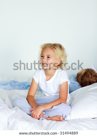 Smiling blonde girl sitting on a big bed - stock photo