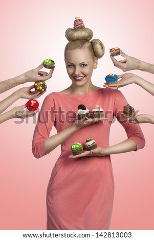 smiling blonde girl with one cupcake on the head, surrounded by some hands with colorful cupcakes. She having colored make-up and funny hair-style - stock photo
