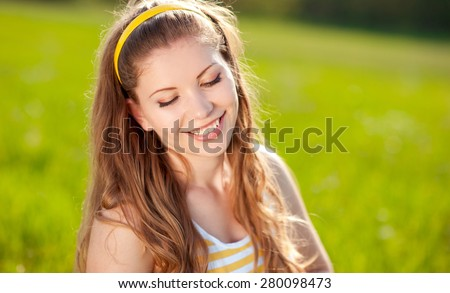 Smiling blonde girl 20-22 year old posing over green outdoors. Positive emotions. Young adults. Summer time. - stock photo