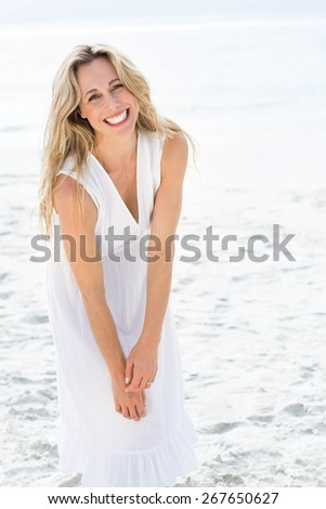 Smiling blonde in white dress looking at camera at the beach - stock photo