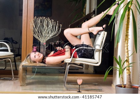 Smiling blonde lying on the glass table - stock photo