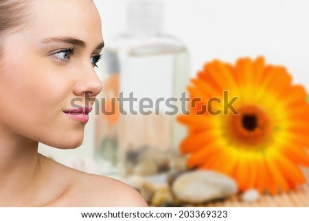 Smiling blonde natural beauty against flower with beauty products - stock photo