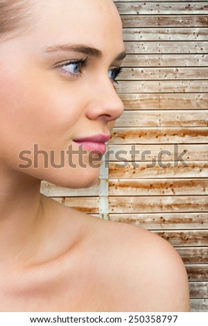 Smiling blonde natural beauty against wooden background in pale wood - stock photo