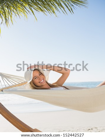Smiling blonde relaxing on hammock at the beach - stock photo